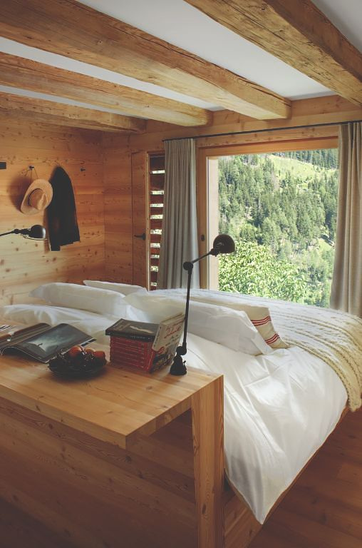 a contemporary organic bedroom clad with light-stained wood, with wooden beams, a bed with a built-in desk and simple textiles