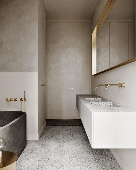 a contemporary to minimalist bathroom done in neutrals, with a large mirror in a gold frame, with a stone slab double sink and a dark stone bathtub, gold fixtures is chic