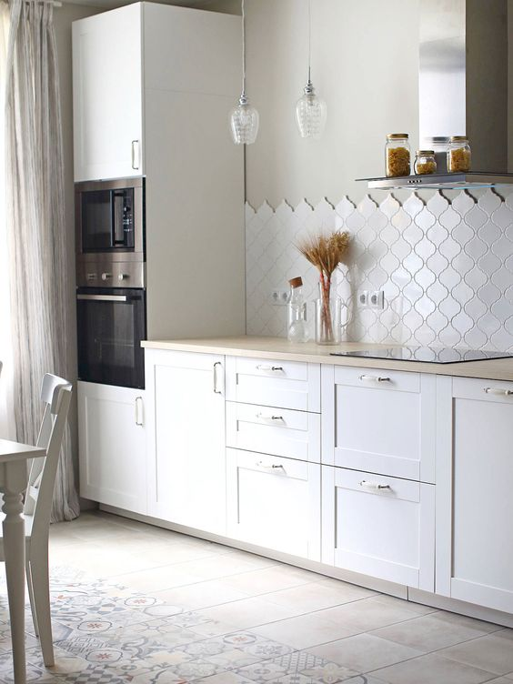 a contemporary white kitchen with shaker cabinets, butcherblock countertops, a white arabesque tile backsplash, pendant bulbs is chic
