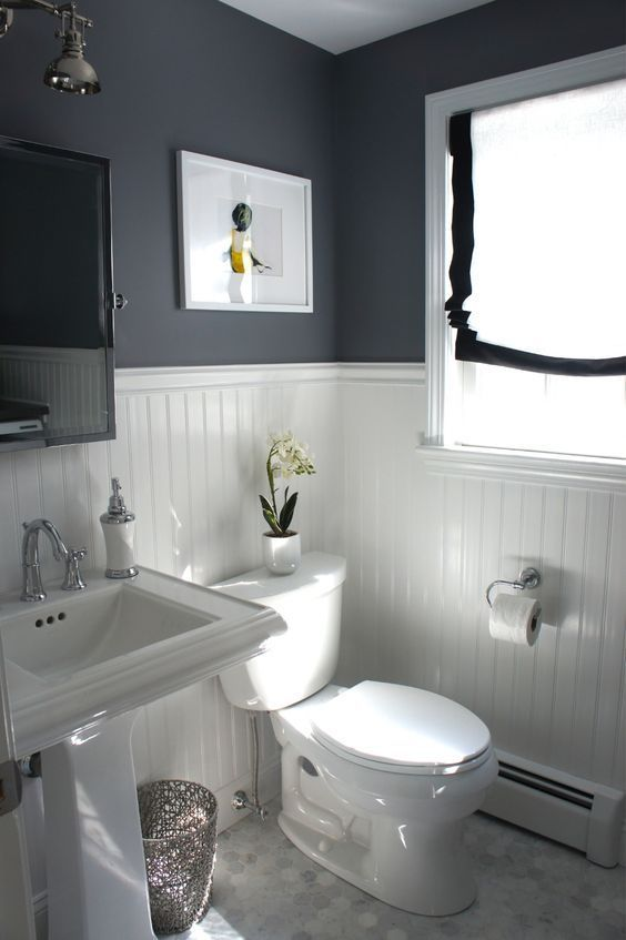 a contrasting bathroom with black walls, white paneling, a pedestal sink, a mirror cabinet and a black and white shade on the window