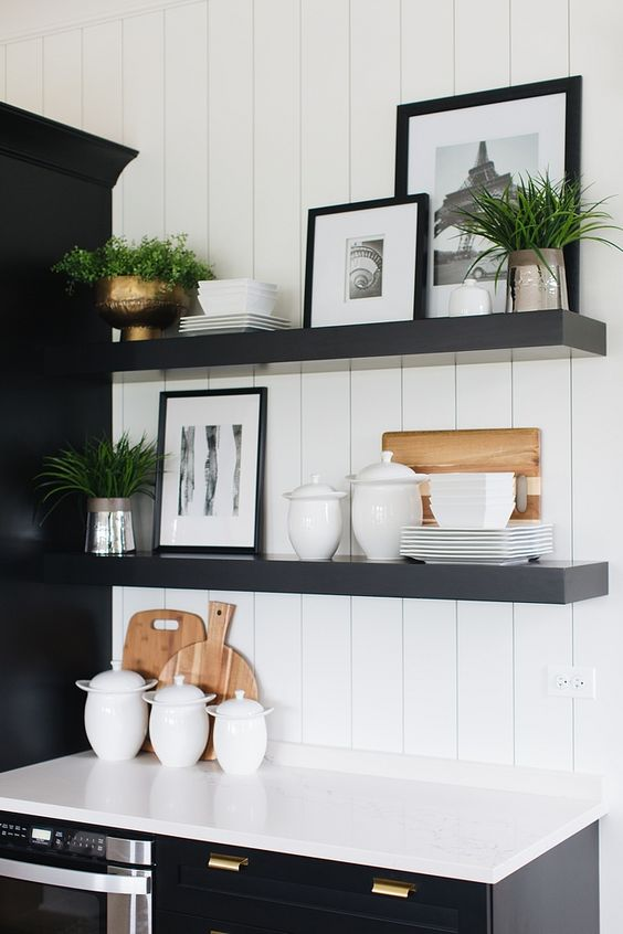 a contrasting kitchen with black cabinets, white countertops and a backsplash, thick black shelves and potted plants