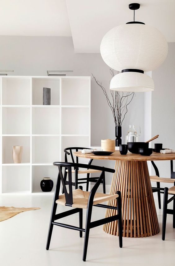 a cool Japandi dining room with a large white storage unit, a round table, black and neutral chairs, a pendant lamp and black tableware