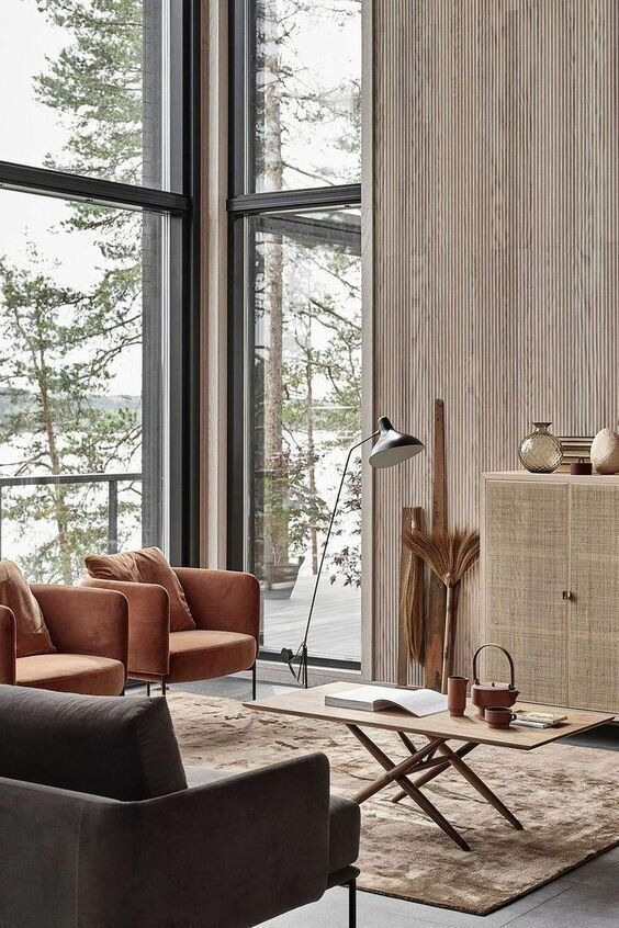 a cool Japandi living room with a view of the lake, rust chairs and a chocolate sofa, a rattan cabinet and a mini coffee table