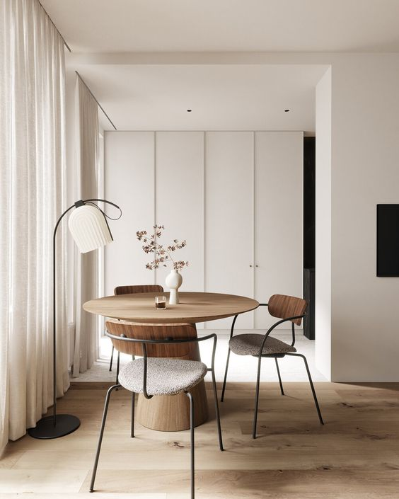 a cool Japandi space done in neutrals, with a round table and cool chairs, a floor lamp and a large sleek storage unit
