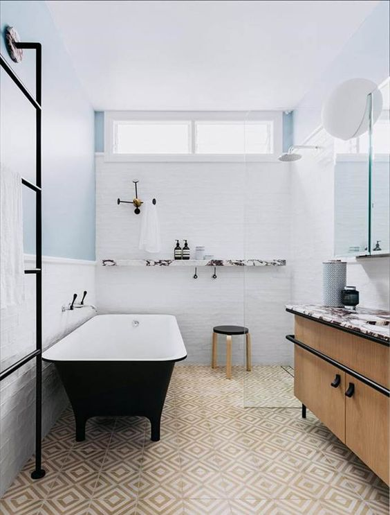 a cool bathroom clad with tan and neutral geo tiles and white ones, with a black cathily shaped bathtub, a large vanity and open shelves