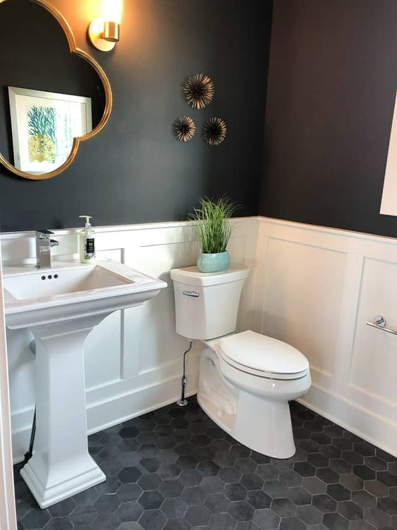 a cool contrasting bathroom with hex tiles, white paneling and black walls, a pedestal sink, a catchily shaped mirror, wall decor and sconces