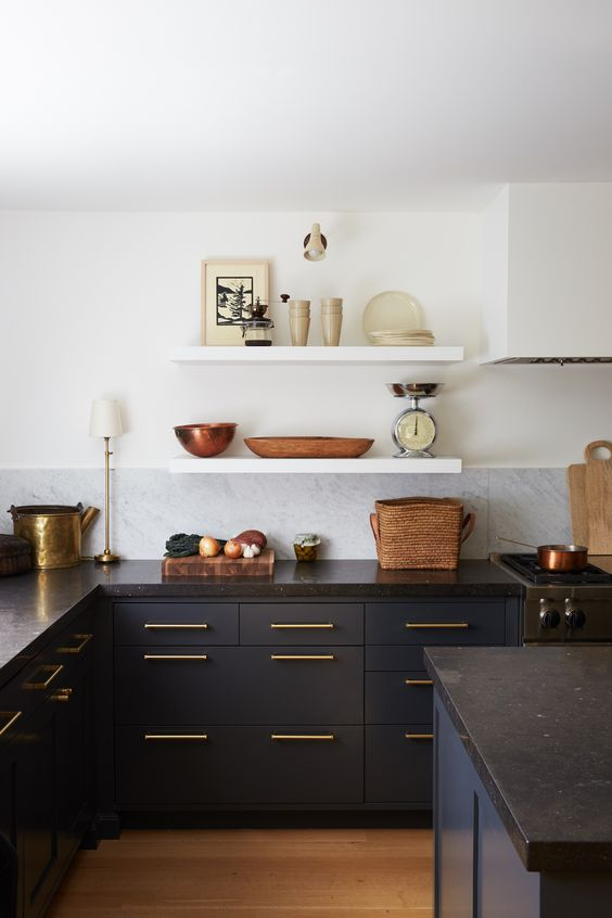 a cool eclectic kitchen with navy lower cabinets and a kitchen island plus white floating shelves instead of upper cabinets