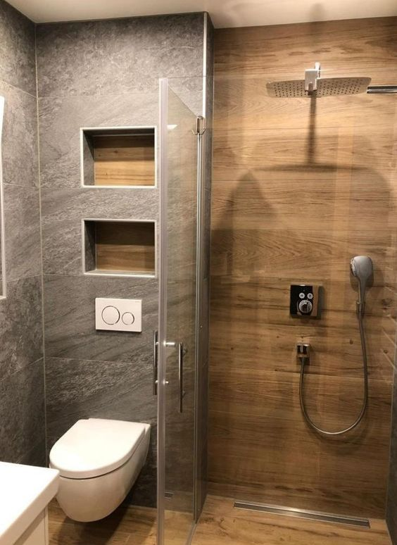 a cool modern bathroom clad with stone and wood look tiles, with niches for storage, white appliances and neutral fixtures