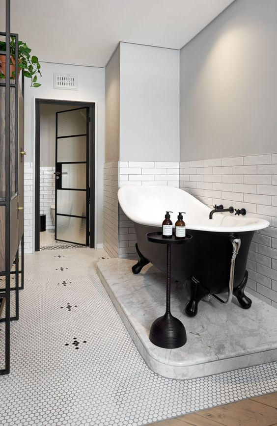 a cool modern bathroom with white subway tiles and penny ones, a black clawfoot tub, a brown vanty and a side table is all chic