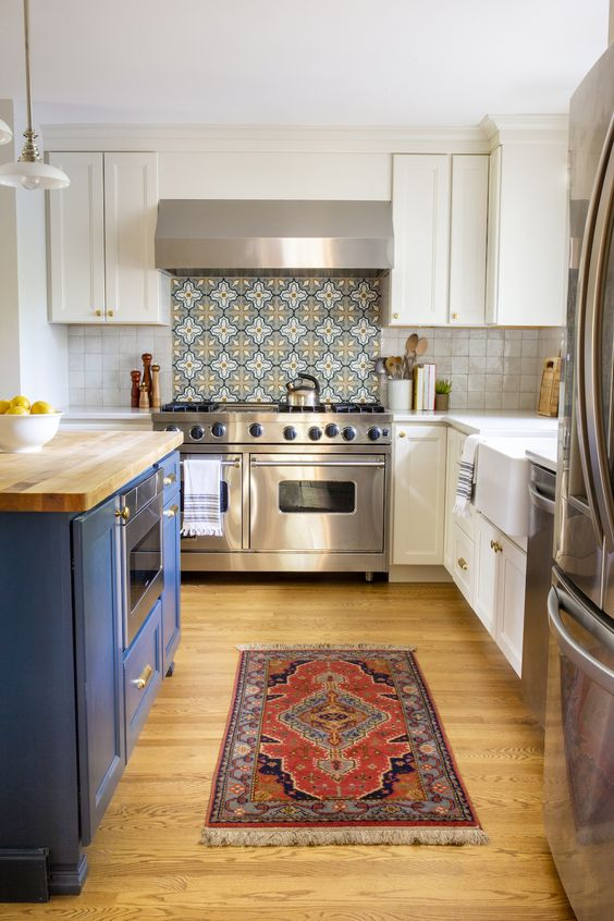 a cottage kitchen with white shaker cabinets and a bold blue kitchen island, white and bold Moroccan tiles on the backsplash is cool