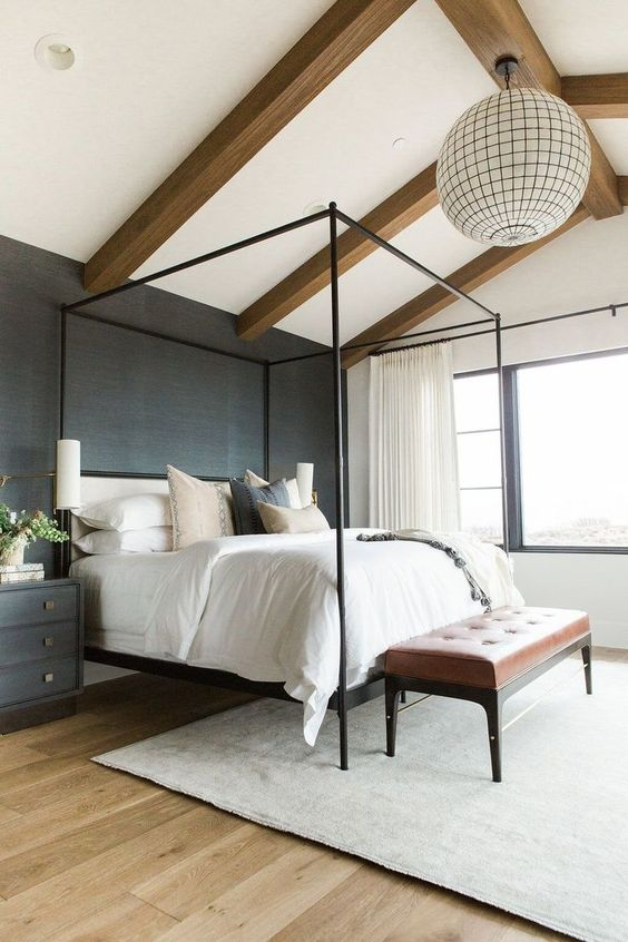 a cozy modern bedroom with a black accent wall, wooden beams on the ceiling, a sphere lamp, a canopy bed and a leather bench