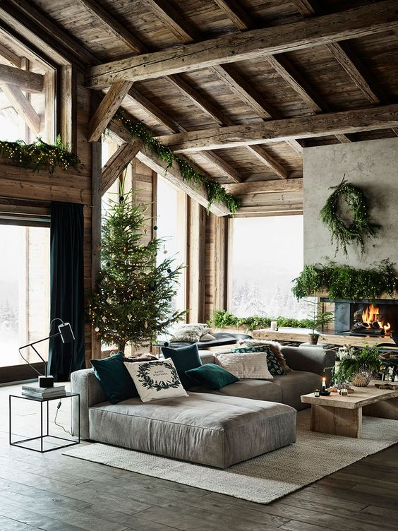 a cozy modern rustic living room with a fireplace, a grey sectional, a wooden coffee table and lots of evergreens for Christmas