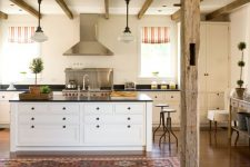 a cozy rustic chic kitchen with neutral cabinets, black countertops, wooden beams and pendant lamps plus bright textiles
