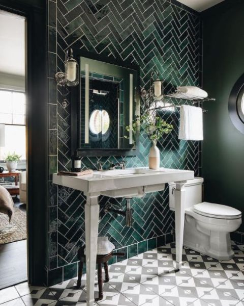 a dark and chic bathroom clad with geo and chevron tiles, a console sink, a mirror, sconces and white appliances is cool