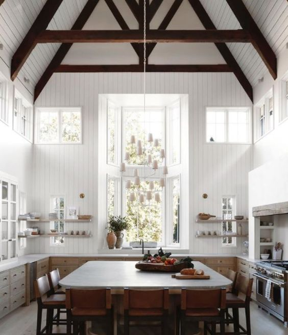 a double-height kitchen with dark stained wooden beams, light-stained cabients, a large table in its center and leather stools