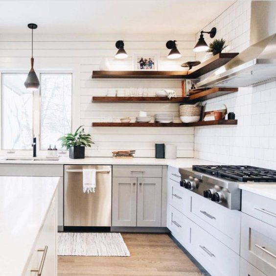 a dove grey farmhouse kitchen with white planked walls, dark stained floating shelves and black lamps