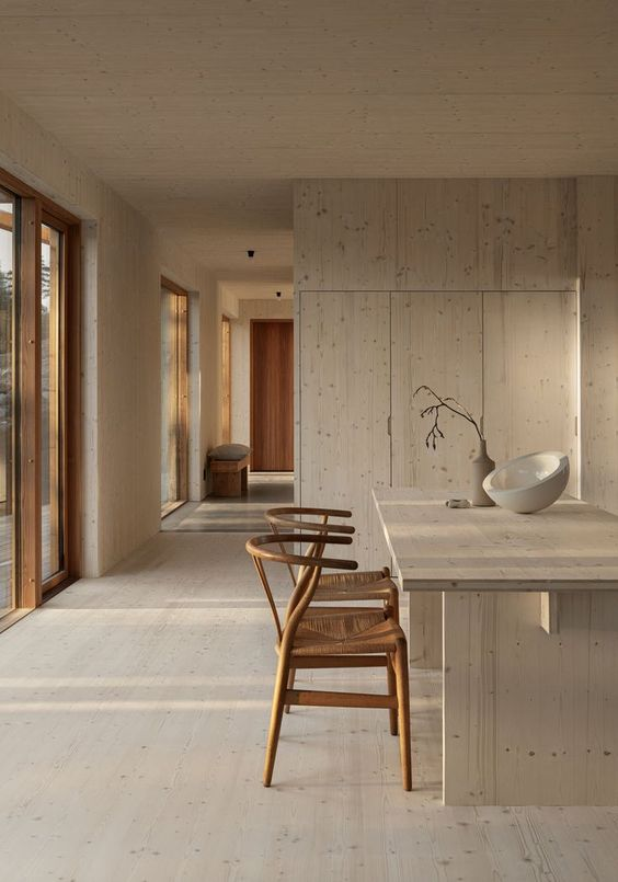a dreamy Japandi kitchen with sleek cabinets, a large kitchen island, woven chairs and large floor to ceiling windows