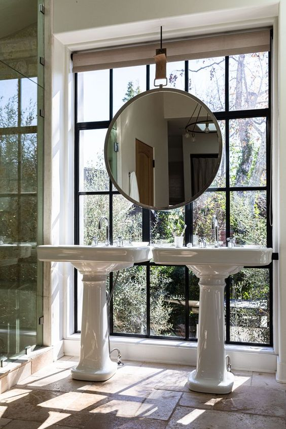 a fab bathroom with a stone floor, a shower enclosed in glass, a window wall for a garden view, two pedestal sinks and a mirror hanging right over the window
