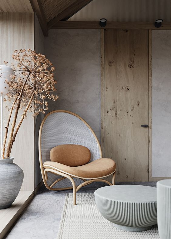 a fabulous living room done in Japandi style, with a rounded chair, round coffee tables and some statement branches in a vase