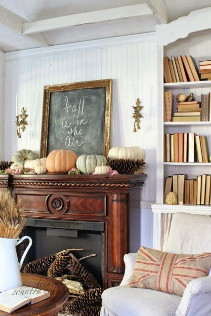 a fall woodland mantel with oversized pinecones and pumpkins, branches and a chalkboard sign is a lovely and pretty idea