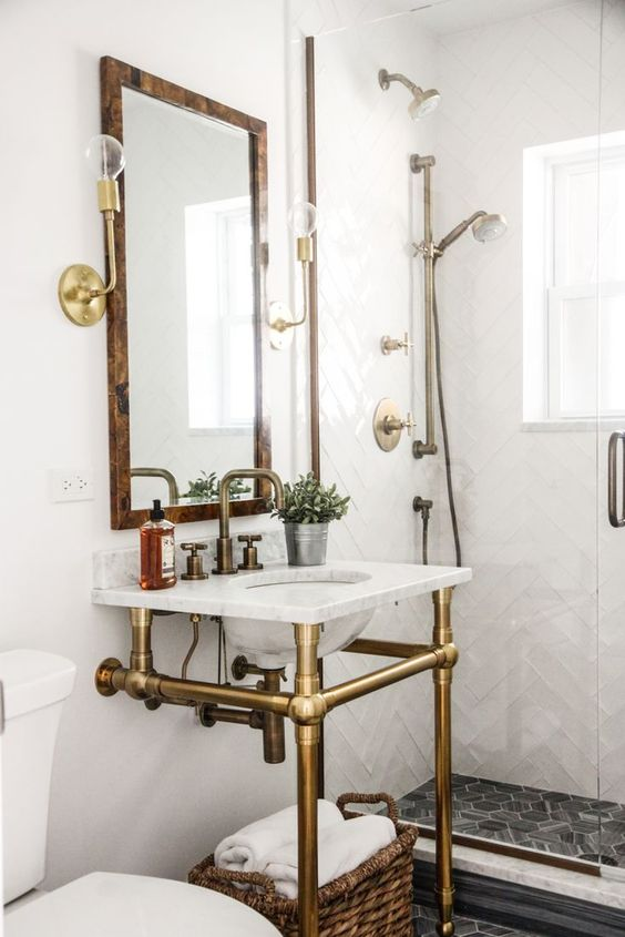 a farmhouse bathroom clad with chevron and hex tiles, a console sink, a mirror with a wooden frame, gold fixtures and touches