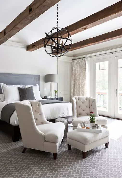 a farmhouse bedroom in neutrals,w ith rich-stained wooden beams, a metal sphere chandelier, a grey bed and creamy chairs, a printed rug