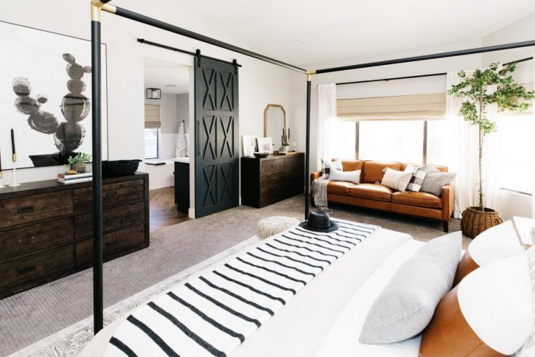 a farmhouse bedroom with a canopy bed, dark stained dressers, an amber leather sofa, artworks and a mirror