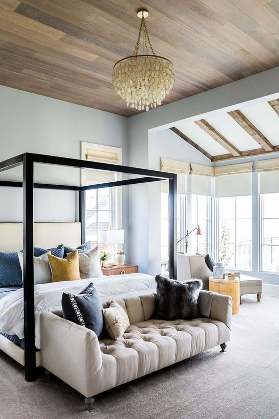 a farmhouse bedroom with light blue walls, a canopy bed, a sofa, a neutral lounger, a tree stump and a shell chandelier