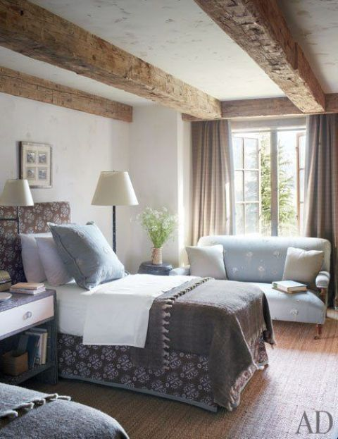 a farmhouse guest bedroom with reclaimed wooden beams, upholstered beds, printed and neutral bedding and various lamps
