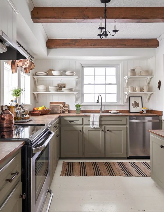 a farmhouse kitchen with olive green cabinetry, butcherblock countertops, wooden beams that echo with them and open shelving