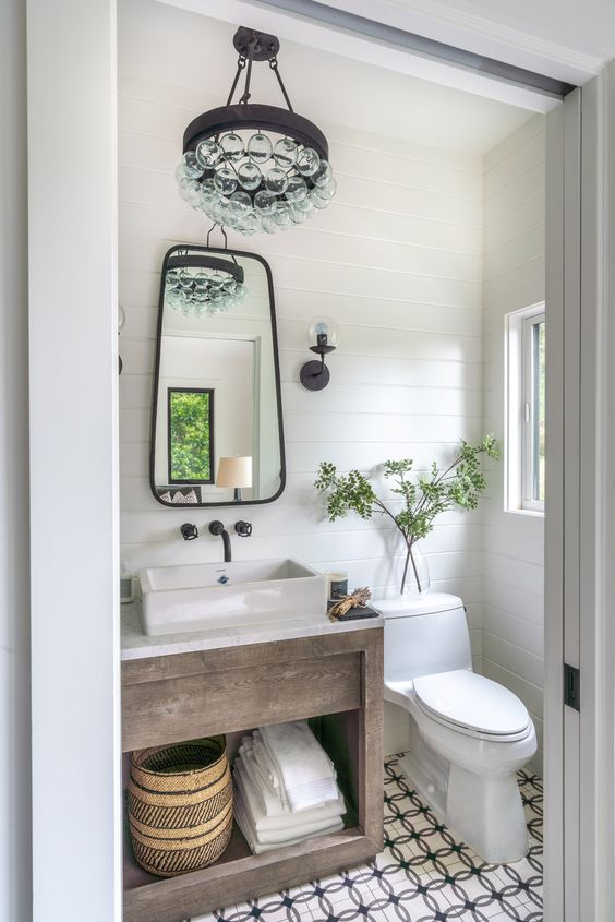 a farmhouse powder room with a patterned tile floor, a wooden vanity, a white square vessl sink, a catchy mirror and a bubble chandelier