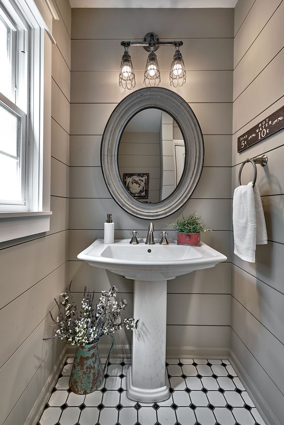 a farmhouse powder room with grey planked walls, a pedestal sink, an oval mirror in a wide frame, a sconce, a towel holder and a sign
