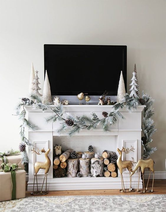 a faux fireplace styled for Christmas, with firewood, pinecones, gold deer, a whitewashed evergreen garland with pinecones and pretty trees