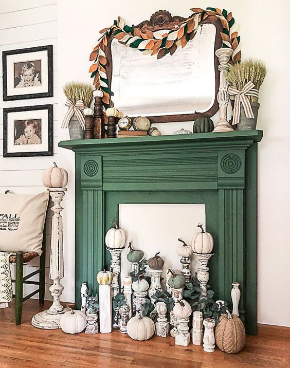 a faux fireplace with a green mantel, an arrangement of pumpkins on tall stands, eucalyptus, wheat and pumpkins on the mantel