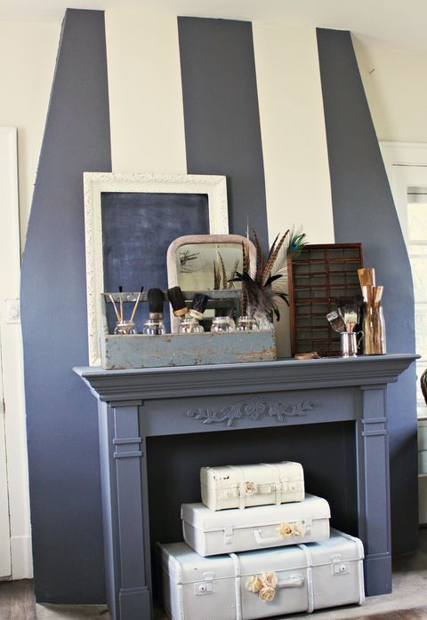 a faux fireplace with a refined mantel, bottles, brushes, vases and whitewashed stacked suitcases inside the fireplace