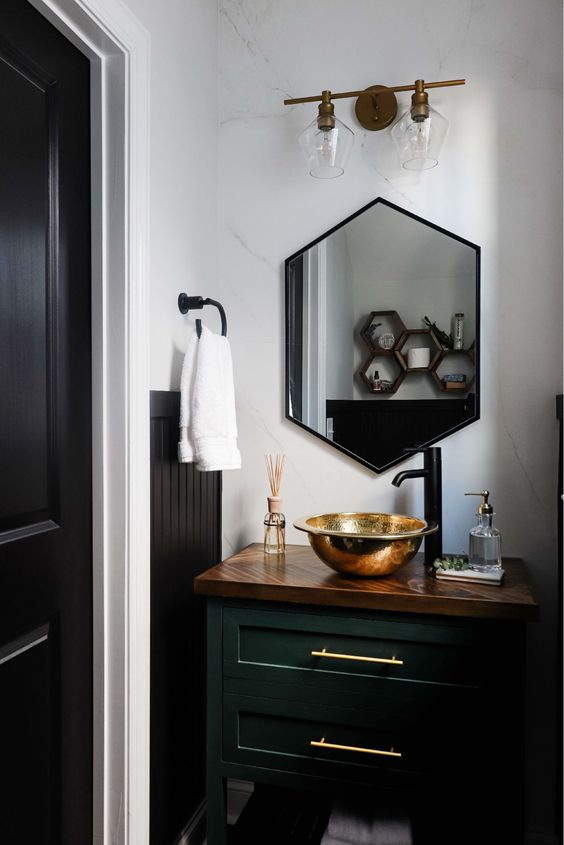 a glam powder room with a dark green vanity, a gold vessel sink, a hexagon mirror in a black frame, neutral nextiles and a large sconce