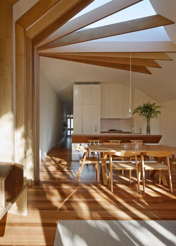 a gorgeous Japandi space with light-stained wooden floors, a dining set, wooden beams on the ceiling with a skylight is very airy