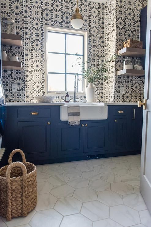 a gorgeous bold blue farmhouse kitchen with pretty Moroccan tiles on the walls and a backsplash, with open shelves and marble hex tiles on the floor
