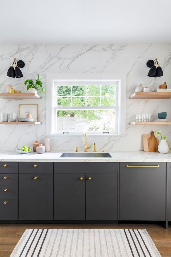 a graphite grey kitchen with a white stone countertop and a wall, light-stained floating shelves and gold fixtures