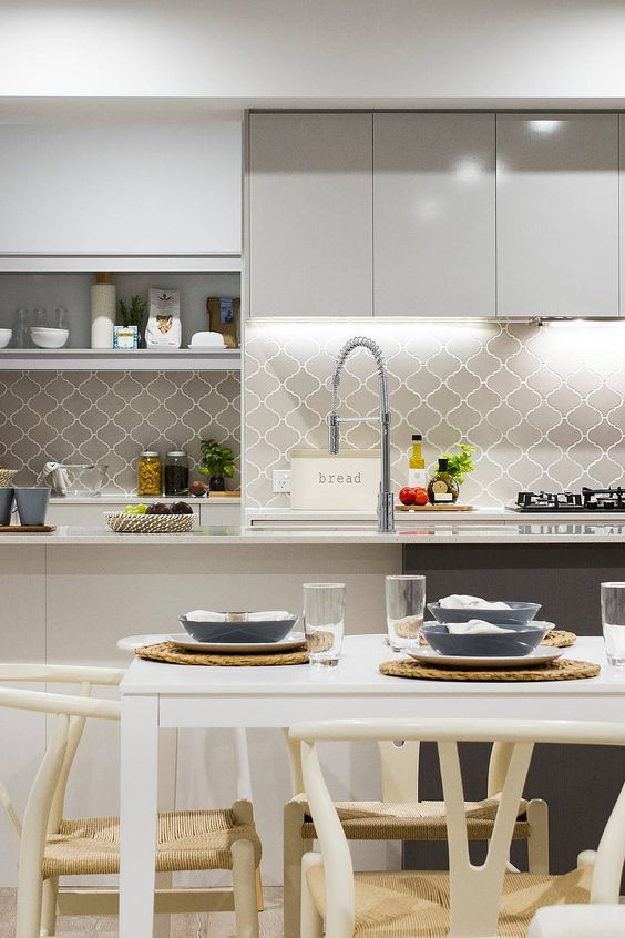 a grey and white contemporary kitchen with a grey arabesque tile backsplash, built-in lights and open storage shelves