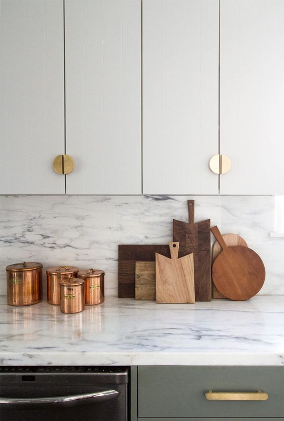 a grey and white kitchen with elegant gold knobs, with white marble countertops and a backsplash, with copper jars is a chic idea