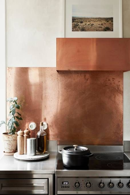 a grey kitchen with white stone countertops, a copper backsplash and a hood looks stylish, bold and modern