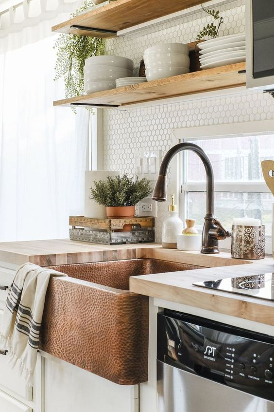 a hammered copper built-in sink and butcherblock countertops add a textural touch to the kitchen and make it very eye-catchy