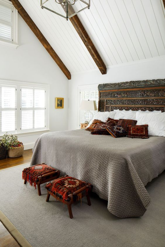 a historic farmhouse bedroom with rich-stained wooden beams, a bed with a carved headboard, neutral bedding and bold pillows, bold printed stools