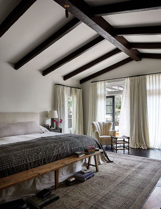 a large and cool neutral bedroom with dark wooden beams on the ceiling, a neutral bed, a wodoen bench and neutral textiles