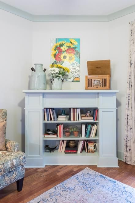 a light blue faux fireplace with books and vases, with churns ont he mantel and a bright artwork is a very pretty idea