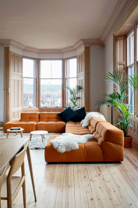 a light-filled living room with gorgeous views of the city, an orange sectional, round coffee tables and dark pillows
