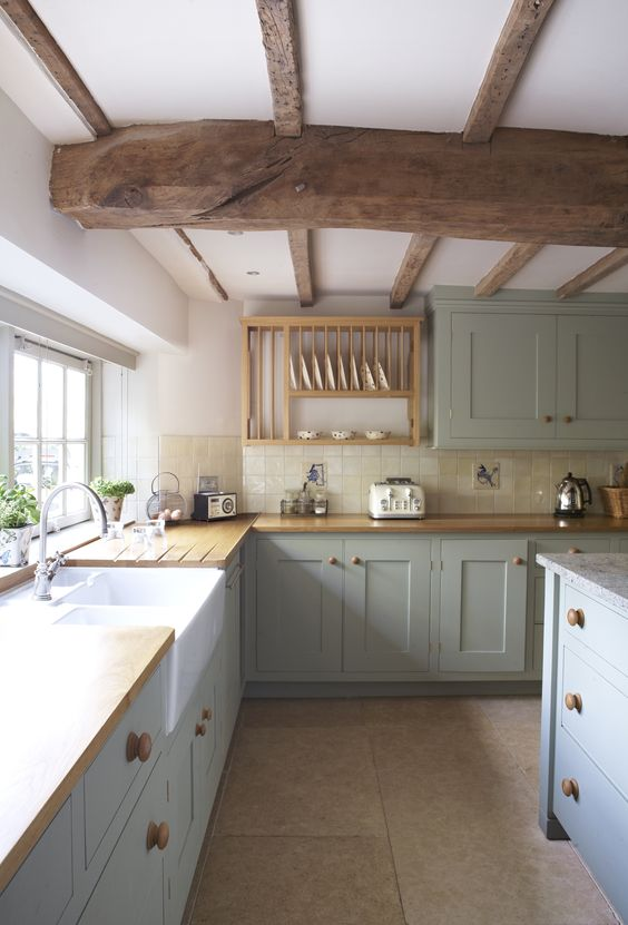 a light grey kitchen with shaker cabinets, butcherblock countertops, wooden beams on the ceiling and some open shelving