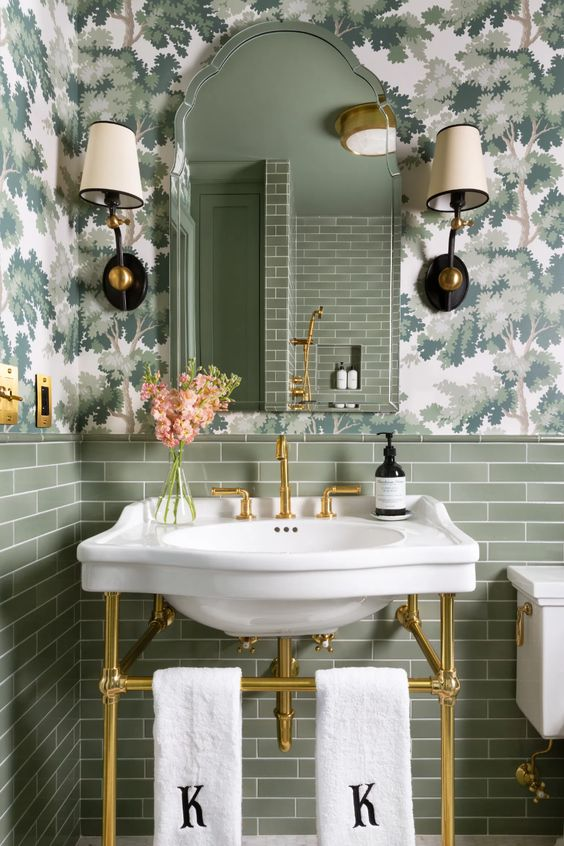a little and pretty powder room with floral print wallpaper, green tiles, an arched mirror, a console sink and vintage sconces
