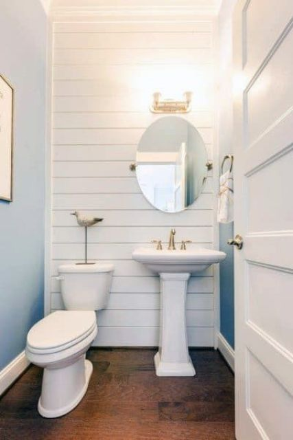 a little coastal powder room with blue walls and a white planked wall, a pedestal sink, touches of brass and gold for a more chic look